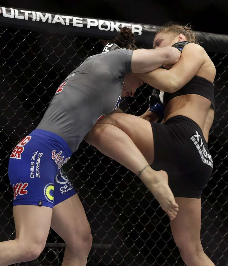Ronda Rousey, right, knees Sara McMann during a UFC 170 mixed martial arts women's bantamweight title fight on Saturday, Feb. 22, 2014, in Las Vegas. Rousey won by TKO. (AP Photo/Isaac Brekken) Photo: Isaac Brekken, Associated Press