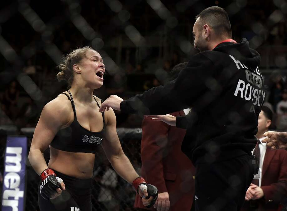 Ronda Rousey, left, goes to hug her trainer Edmond Tarverdyan after defeating Sara McMann in a UFC 170 mixed martial arts women's bantamweight title fight on Saturday, Feb. 22, 2014, in Las Vegas. (AP Photo/Isaac Brekken) Photo: Isaac Brekken, Associated Press