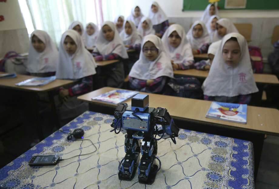 Veldan, a humanoid praying robot built by Iranian schoolteacher Akbar Rezaie, performs morning prayer in front of Alborz elementary school girls in the city of Varamin, Iran. Photo: Vahid Salemi / Associated Press / AP