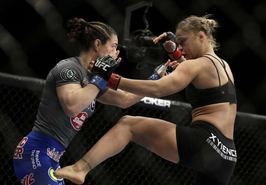 Ronda Rousey, right, kicks Sara McMann during a UFC 170 mixed martial arts women's bantamweight title fight on Saturday, Feb. 22, 2014, in Las Vegas. Rousey won by TKO. (AP Photo/Isaac Brekken) Photo: Isaac Brekken, Associated Press