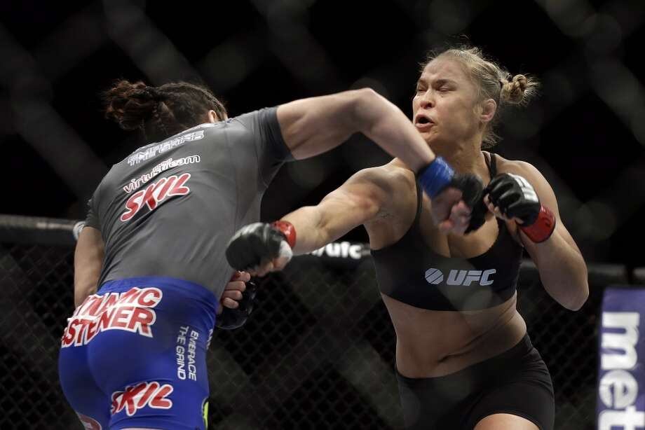 Ronda Rousey, right, and Sara McMann exchange punches during a UFC 170 mixed martial arts women's bantamweight title fight on Saturday, Feb. 22, 2014, in Las Vegas. (AP Photo/Isaac Brekken) Photo: Isaac Brekken, Associated Press