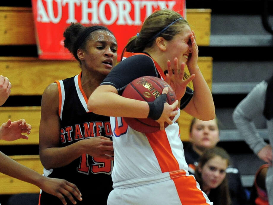 Stamford's Anisa Fortt, left, fouls Danbury's Allie Smith while attempting to steal the ball, during FCIAC Girls' Basketball Semi-final action in Fairfield, Conn. on Tuesday February 25, 2014. Photo: Christian Abraham / Connecticut Post