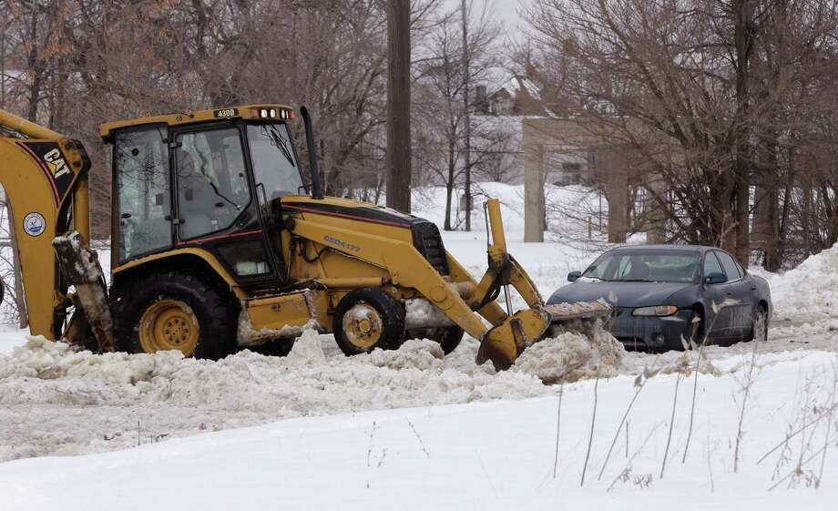"""FILE - This Feb. 11, 2014 file photo shows work crews clearing ice off the road as water continues to spew from a broken water main in Detroit. The broken water main flooded a several-block area in southwest Detroit, trapping several cars. A new winter """"misery index"""" confirms what many Americans in the Midwest and East know in their all-too-chilled bones and snow-covered driveways: This has been one of the harshest winters of a lifetime. And just like in the great recession of 2008, nowhere in the nation has been hit relatively harder than Detroit. Sure Chicago, Indianapolis and Philadelphia and Moline are in the midst of their third most extreme winters in more than 60 years, according to a winter extremity index created by a National Weather Service meteorologist. (AP Photo/Carlos Osorio, File) ORG XMIT: WX113 Photo: Carlos Osorio / AP"""