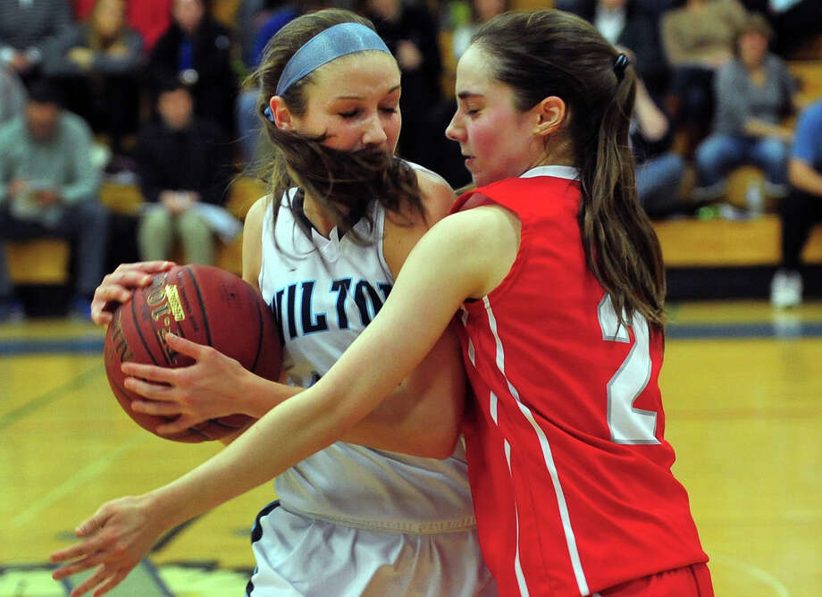 Greenwich's Caroline Beneville, right, blocks Wilton's Haley English, during FCIAC Girls' Basketball Semi-final action in Fairfield, Conn. on Tuesday February 25, 2014. Photo: Christian Abraham / Connecticut Post