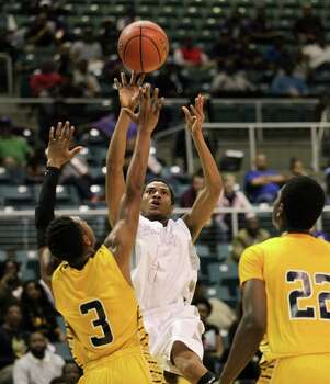 Wheatley's Gerald Thomas shoots over Marshall's Jadier  Richardson (3) and Elliot Taylor (22) during a high school boys basketball regional quarterfinal playoff game between Fort Bend Marshall and Wheatley at the Merrill Center in Katy, Texas . Photo: Bob Levey / ©2014 Bob Levey