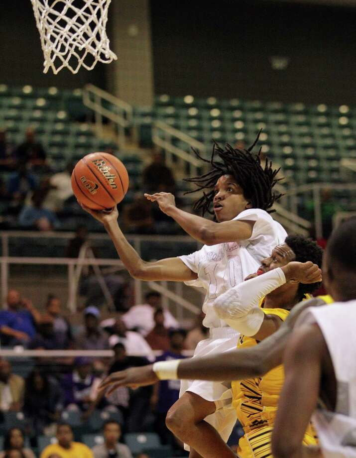 Wheatley's Kevon Johnson drives to the basket during a high school boys basketball regional quarterfinal playoff game between Fort Bend Marshall and Wheatley at the Merrill Center in Katy, Texas . Photo: Bob Levey / ©2014 Bob Levey