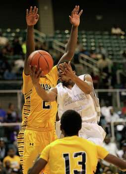 Wheatley's Gerald Thomas (4) drives past Marshall's Jeremy Smith (2) during a high school boys basketball regional quarterfinal playoff game between Fort Bend Marshall and Wheatley at the Merrill Center in Katy, Texas . Photo: Bob Levey / ©2014 Bob Levey