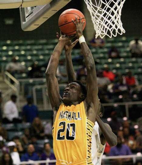 Marshall's Christian Barrett puts back an offensive rebound during a high school boys basketball reg