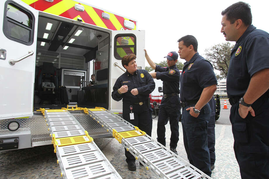 EMS chief Yvette Granato explains the workings of new style ramps as the SAFD unveils its new fleet of ambulances by rolling out 16 of the units at SAPD headquarters on February 25, 2014. Photo: For The San Antonio Express-News