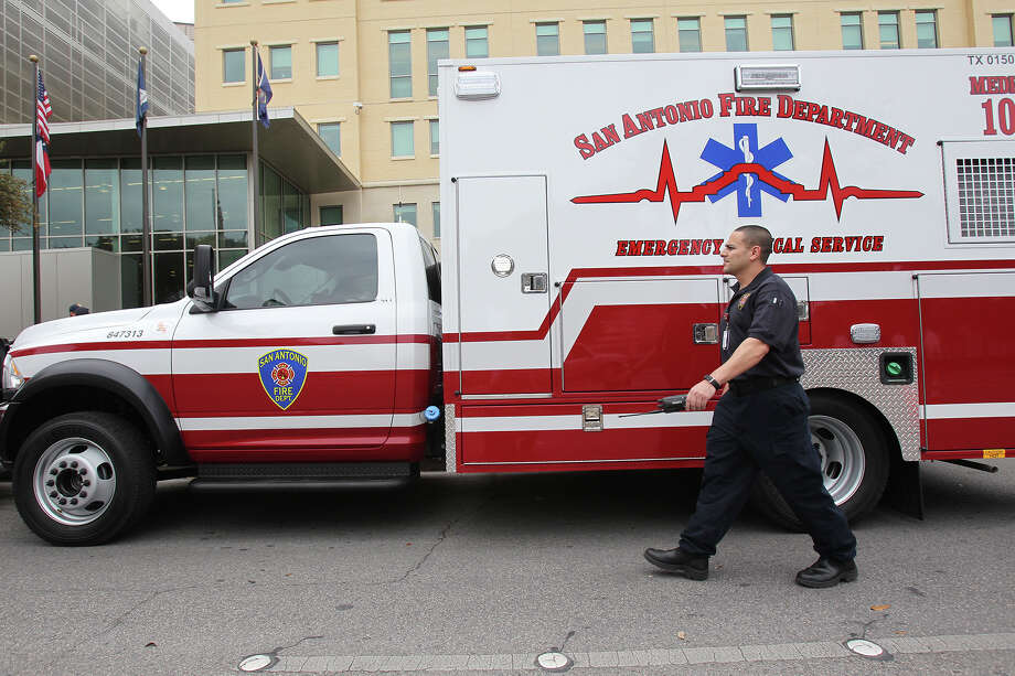 An EMS technician walks by a new vehicle as the SAFD unveils its new fleet of ambulances by rolling out 16 of the units at SAPD headquarters on February 25, 2014. Photo: For The San Antonio Express-News