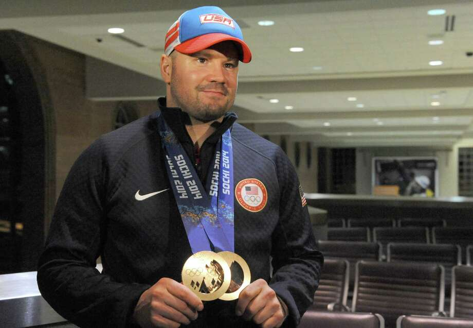 Bobsledder Steve Holcomb, winner of 2 Olympic bronze medals in Sochi, is traveled through the Albany Airport on Tuesday Feb. 25, 2014 in Colonie, N.Y. Holcomb, and teammate Steve Langton, were the only 2 US Olympians in Sochi to score individual medals in 2 events.Holcomb spends much of his time training and preparing for competition in Lake Placid.(Michael P. Farrell/Times Union) Photo: Michael P. Farrell / 00025890A