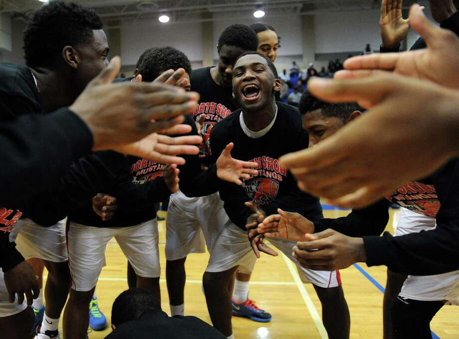 North Shore's Dominique Poledore, center, gets his teammates fired up before the Class 5A Region 3 quarterfinal high school basketball playoff game against Manvel, Tuesday, February 25, 2014, at Clear Springs High School in League City, TX. Photo: Eric Christian Smith, For The Chronicle