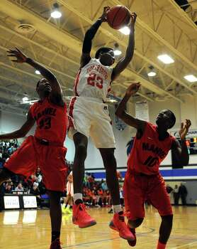 North Shore's Kerwin Roach, center, grabs a rebound past Manvel's Kelton Houston, left, and Kion White during the first half of the Class 5A Region 3 quarterfinal high school basketball playoff game, Tuesday, February 25, 2014, at Clear Springs High School in League City, TX. Photo: Eric Christian Smith, For The Chronicle