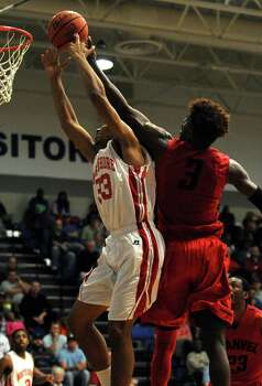 North Shore's Chukuemeke Egbule, left, fights for a rebound with Manvel's Leon Gilmore during the first half of the Class 5A Region 3 quarterfinal high school basketball playoff game, Tuesday, February 25, 2014, at Clear Springs High School in League City, TX. Photo: Eric Christian Smith, For The Chronicle