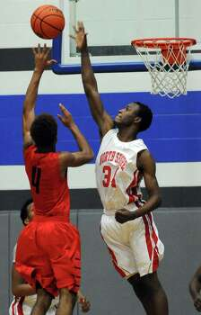 North Shore's Derec Burks, right, blocks the shot of Manvel's Dexter Williams during the first half of the Class 5A Region 3 quarterfinal high school basketball playoff game, Tuesday, February 25, 2014, at Clear Springs High School in League City, TX. Photo: Eric Christian Smith, For The Chronicle
