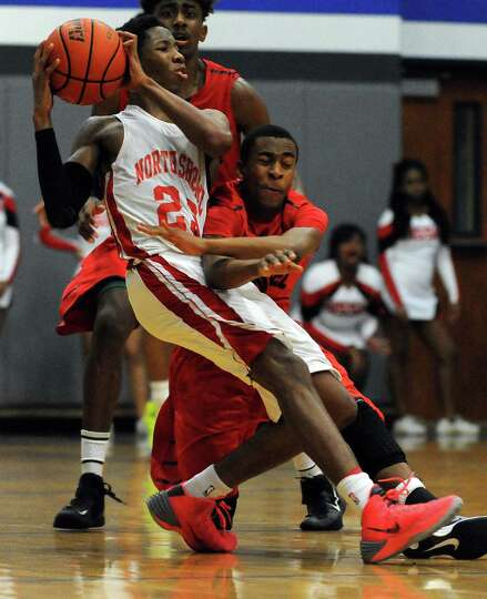 North Shore's Kerwin Roach, left, fights off the defensive pressure of Manvel's Uyran Hudson during