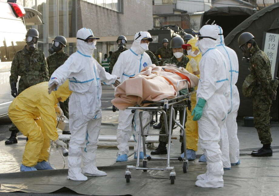 A person who is believed to be have been contaminated with radiation, wrapped with a blanket, is carried to ambulance at a radiation treatment centre in Nihonmatsu city in Fukushima prefecture on March 13, 2011.  (JIJI PRESS/AFP/Getty Images) Photo: JIJI PRESS, AFP/Getty Images / 2011 AFP