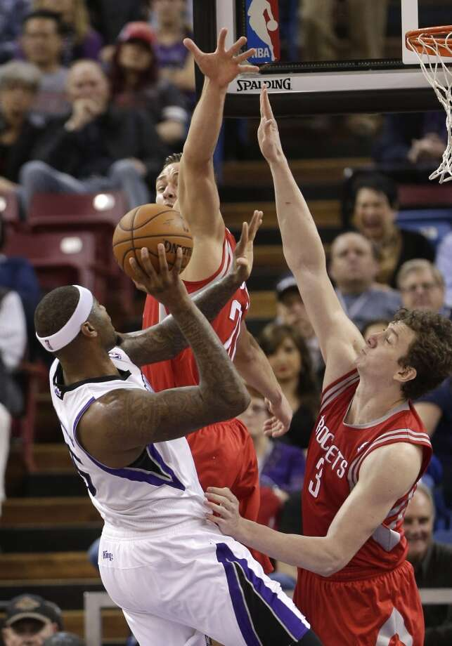 Omer Asik and Donatas Motiejunas of the Rockets defend a shot by Kings forward DeMarcus Cousins. Photo: Rich Pedroncelli, Associated Press