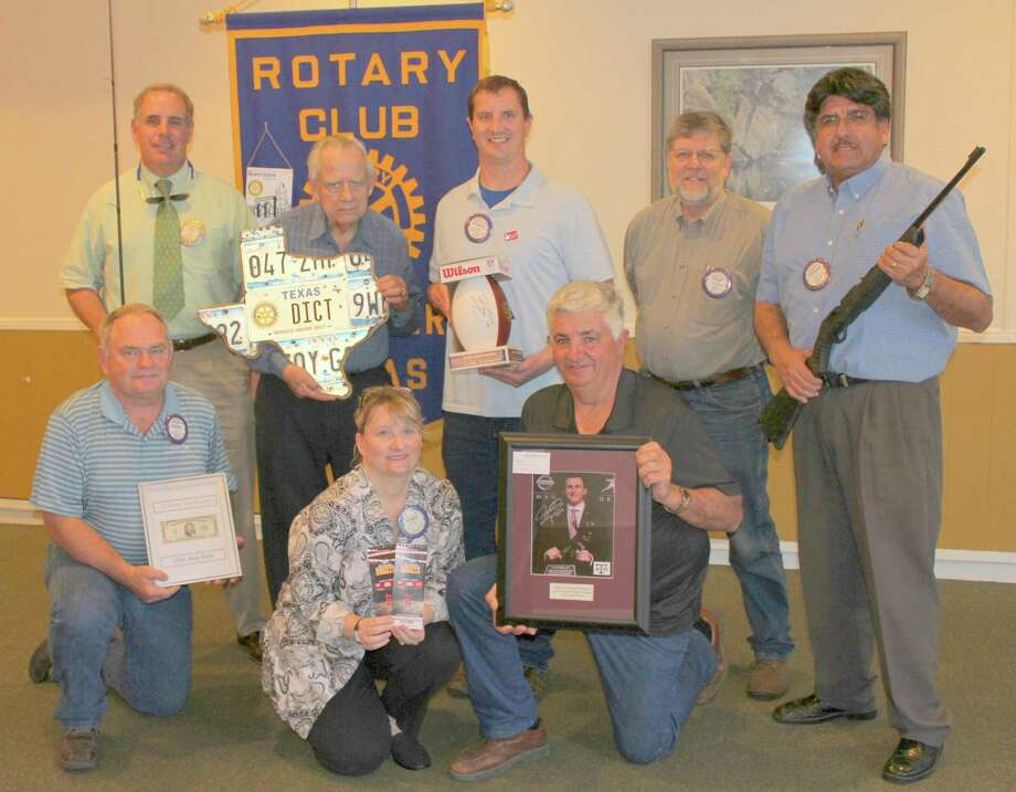 Showing off some of the auction items available this Friday are, bottom row, from left, Hurley Johnson, Ginger Johnson and Gumbo Fest Chairman Tom Stavinoha. Second row, Gary Finch, Stanley Kucherka, Bradley Stavinoha, Hugh Conway and Enrique Ramon. Photo: Rotary Club Of Rosenberg