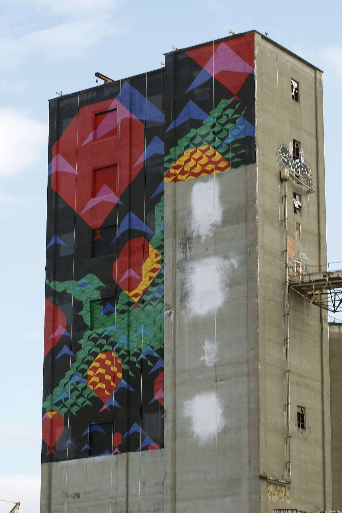 A new waterfront mural called 'Bayview Rise' is seen on an abandoned grain silo at Port Pier 92 in San Francisco, Calif., on Thursday, November 21, 2013. The art is being created in the Bayview by artists Laura Haddadd and Tom Drugan.