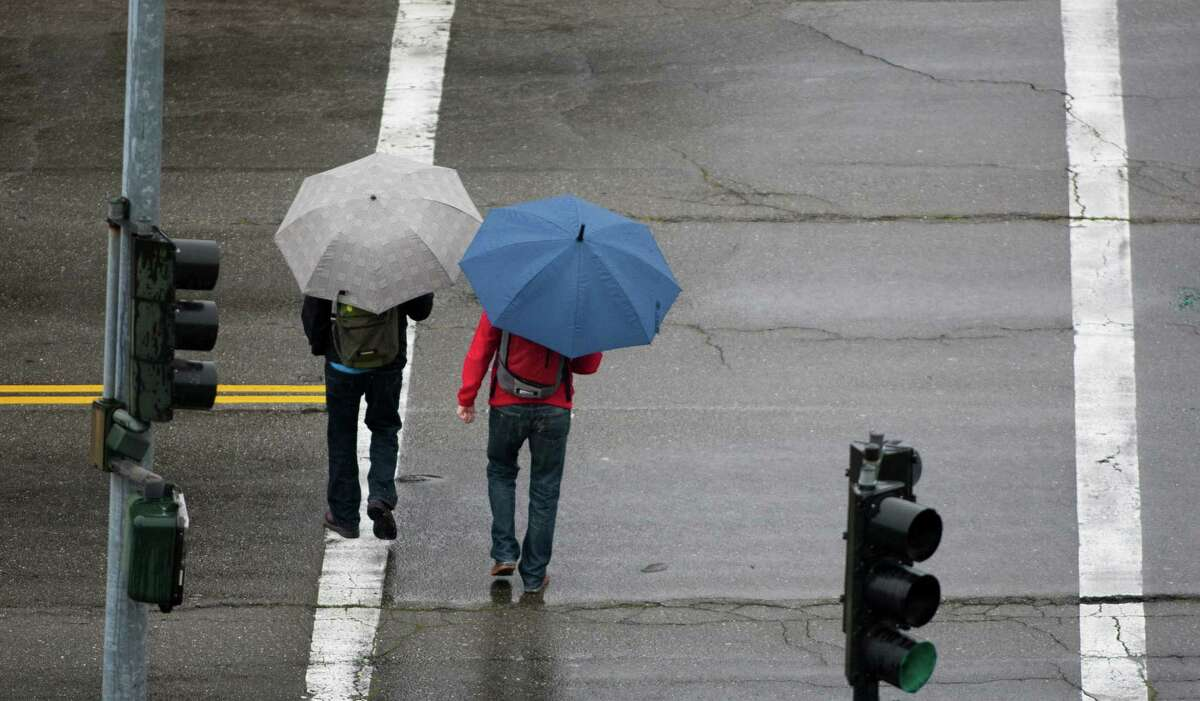 Two pedestrians use umbrellas to shield themselves from a light rainfall Wednesday morning in Oakland.