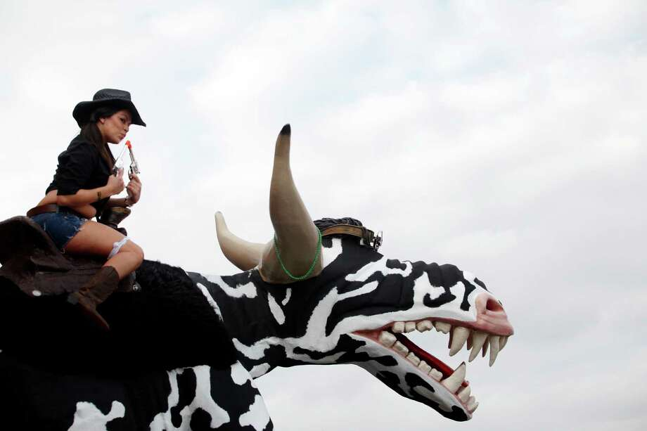 Angelica Pompa, of Houston, poses for a photo on Bovinasarus Tex, outside of the Holy Cow Cookers tent, during the World Championship BBQ contest, Saturday, February 26, 2011, at Reliant Park in Houston, Texas. (Todd Spoth/For the Chronicle) Photo: TODD SPOTH, Freelance / Freelance