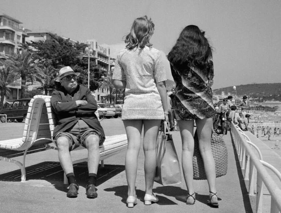 His trousers' legs rolled to take advantage of the sun, a retired man looks toward two girls wearing mini-skirt, 13 July 1969 in Nice, France. Photo: STAFF, AFP/Getty Images