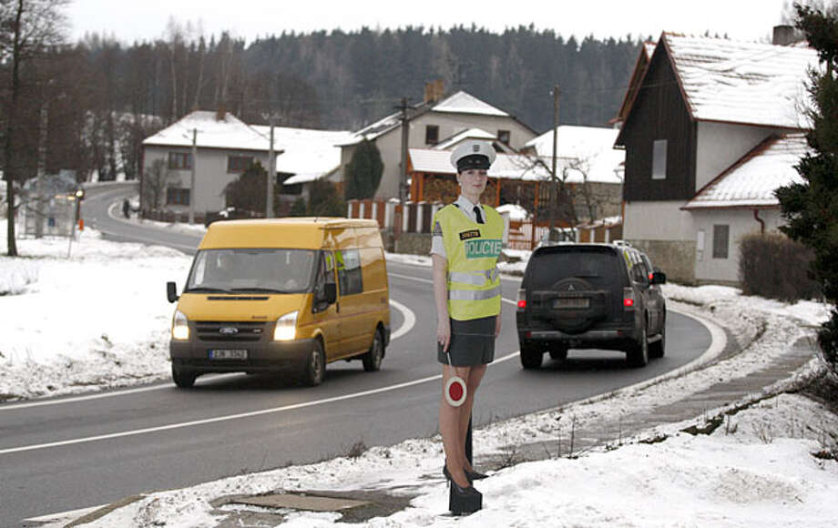 A cardboard police women officer in a mini skirt is displayed to slow down traffic in the village of Myslotin, central Czech Republic, Thursday, Dec. 9, 2010. The Czech Republic, as part of an attempt to slow down traffic and save cash on installing new traffic lights, installed life-sized cardboard cut-outs of a mini-skirted policewoman. Photo: Associated Press