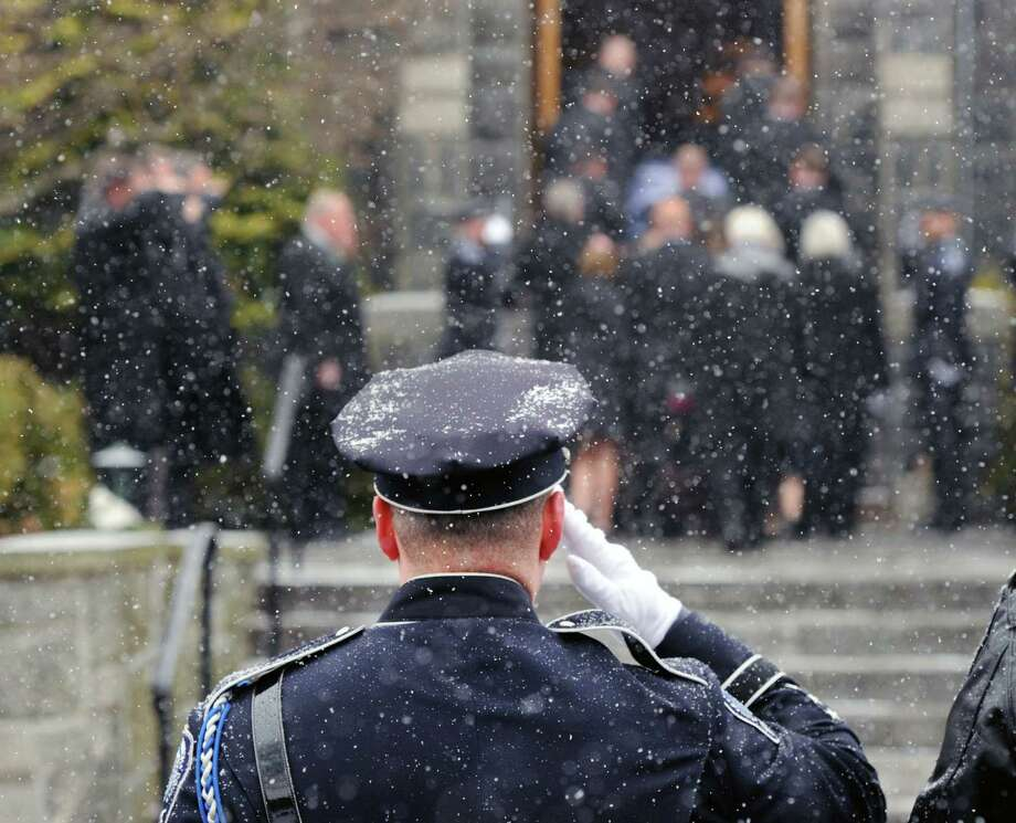 A Greenwich Police Officer salutes during the funeral service for Greenwich Police Sgt. Roger Petrone at St. Mary Church, Greenwich, Wednesday morning, Feb. 26, 2014. Petrone died Thursday at age 44 after a seven year battle with amyotrophic lateral sclerosis, also known as Lou Gehrig's disease. Photo: Bob Luckey / Greenwich Time