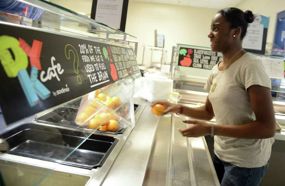 Eighth grade student Angel Holloway grabs an orange at the lunch counter Wednesday, Feb. 26, 2014, at Derby Middle School in Derby, Conn. This week, a new study showed that, between 2003-2004 and 2011-2012, obesity rates among children aged 2 to 5 fell about 40 percent. Some experts have credited the drop to the increased attention nationwide to proper nutrition and physical activity. Photo: Autumn Driscoll / Connecticut Post