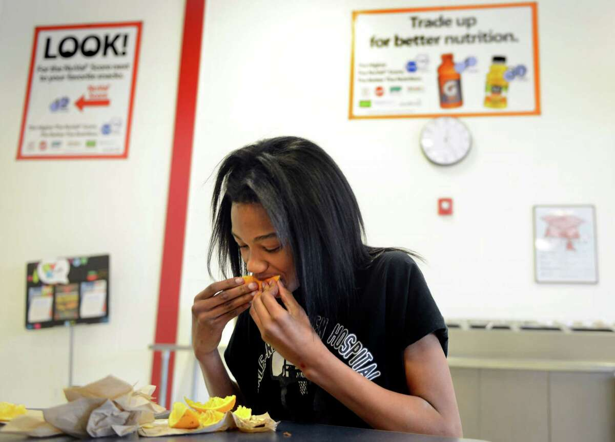 Eighth grade student Iashia Cooper eats an orange after finishing her lunch Wednesday, Feb. 26, 2014, at Derby Middle School in Derby, Conn. This week, a new study showed that, between 2003-2004 and 2011-2012, obesity rates among children aged 2 to 5 fell about 40 percent. Some experts have credited the drop to the increased attention nationwide to proper nutrition and physical activity.