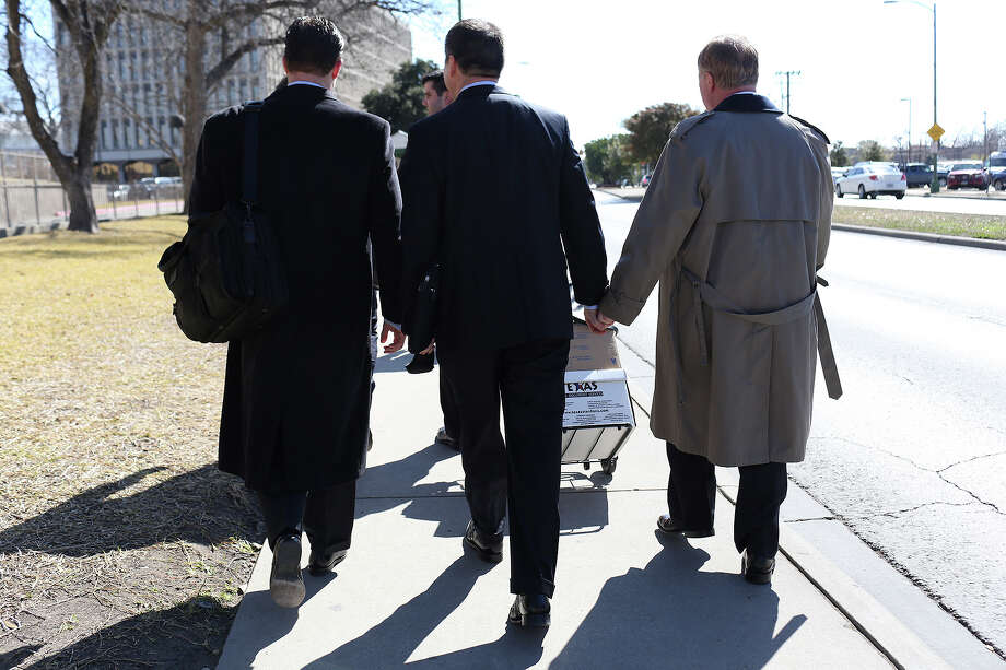 Mark Phariss, right, walks with his partner, Victor Holmes,  after the hearing for their request for a preliminary injunction to declare Texas' ban on same-sex marriage unconstitutional at the John H. Wood, Jr. U.S. Courthouse in San Antonio on Wednesday, Feb. 12, 2014. Photo: LISA KRANTZ, Lisa Krantz / SAN ANTONIO EXPRESS-NEWS