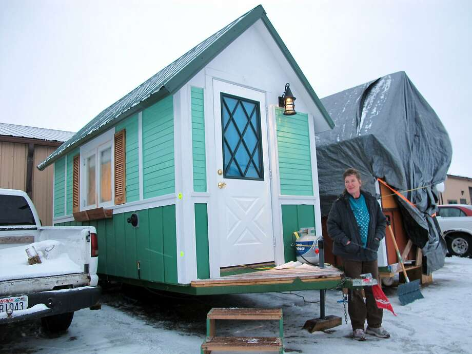 In this Jan. 16, 2014 photo Betty Ybarra, 48, stands outside a tiny houses she and her boyfriend live in, in Madison, Wis. It is the first house built by OM Build, which wants to build nine houses in Madison for the homeless. (AP Photo/Carrie Antlfinger) Photo: Carrie Antlfinger, Associated Press