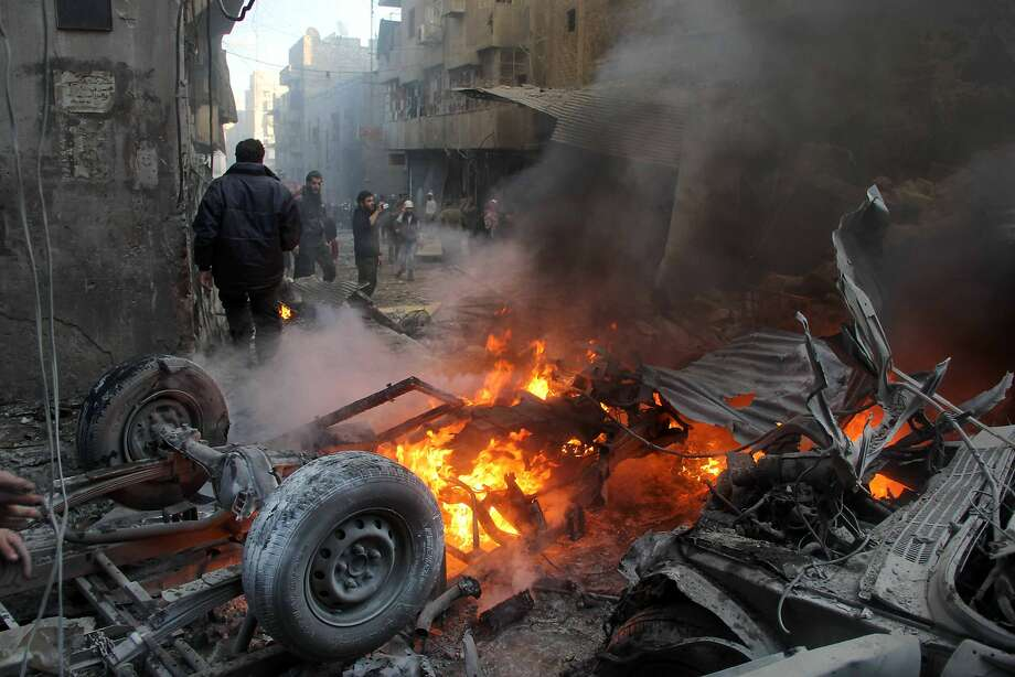 Residents examine  a burning  vehicle  following  government  shelling in Aleppo. Photo: Mohammed Wesam, AFP/Getty Images