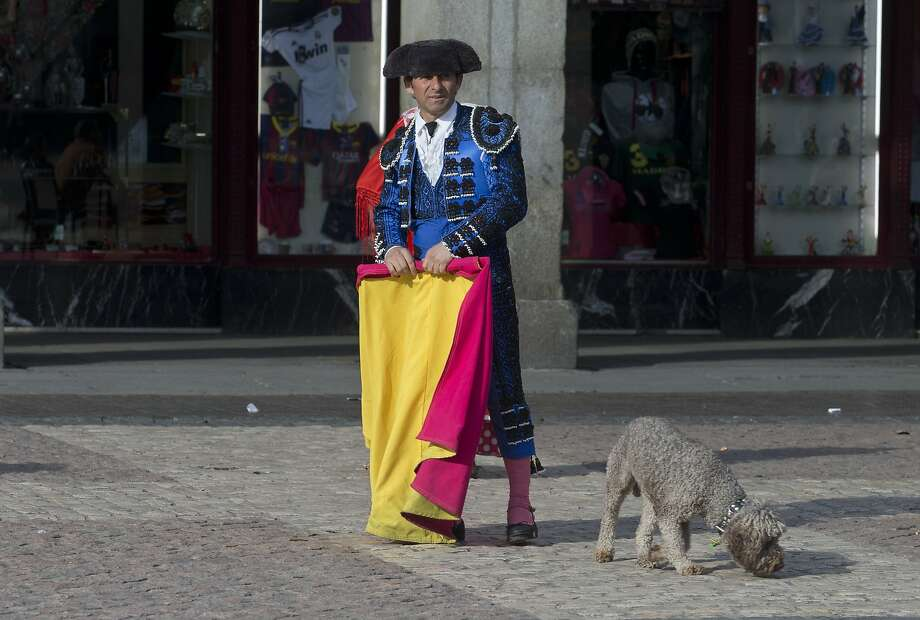 Toro! Toro! Despite waving his cape, a sidewalk matador can't get the bull's attention in 