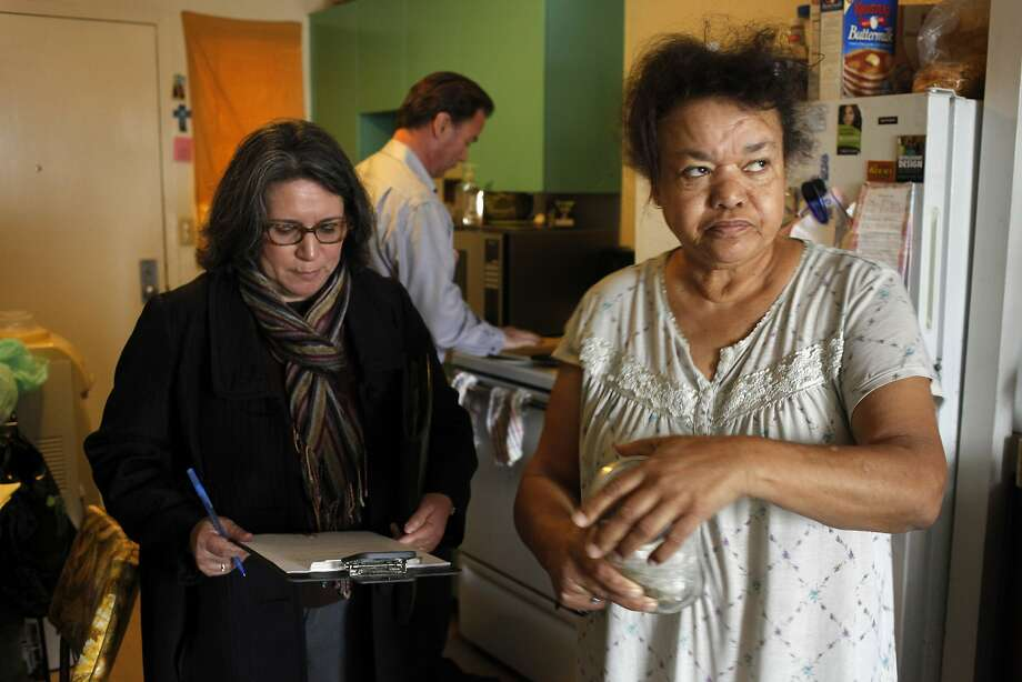 Anna Threadgill (right) shows a jar full of bedbugs to Richmond Housing Authority management analyst Leticia Niles as Michael Petragallo inspects the stove at the Hacienda complex. Photo: Lacy Atkins, The Chronicle