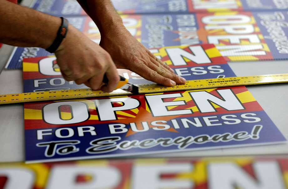 "Tom Cushing of Fast Signs cuts signs reading ""Open for Business to Everyone"" that businesses used to express opposition to the bill that would have allowed them to refuse service to gays on religious grounds. Photo: Matt York, Associated Press"