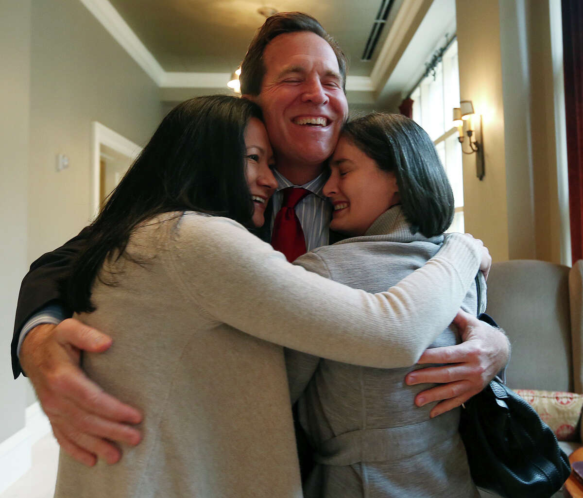Cleopatra De Leon, left, and Nicole Dimetman hug attorney Neel Lane as they react to Federal Judge Orlando Garcia granting a preliminary injunction in their lawsuit against the state to strike down the gay marriage ban, Wednesday, Feb. 26, 2014. Also in the lawsuit are Victor Holmes and Mark Phariss.
