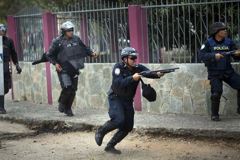 A police officer fires his shotgun to disperse demonstrators during an antigovernment protest in Valencia, Venezuela's third largest city. Photo: Rodrigo Abd, Associated Press