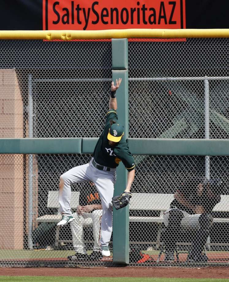 A's right fielder Josh Reddick, (16) climbs the fence to rob Giants' slugger Michael Morse, (38) of a home run in the second inning, as the San Francisco Giants take on the Oakland Athletics in a spring training game at Scottsdale Stadium, in Scottsdale, Arizona on Wednesday Feb. 26, 2014. (Michael Macor/The Chronicle) Photo: Michael Macor, The Chronicle