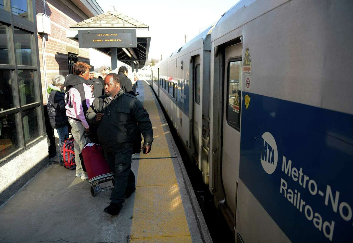 Commuters exit from an off-peak Metro-North train at the Danbury train station in Danbury, Conn. on Wednesday, Feb. 26, 2014. Metro-North is to release a schedule of which trains will switch to bus travel on the Danbury line while workers try to fix the faulty signal system.