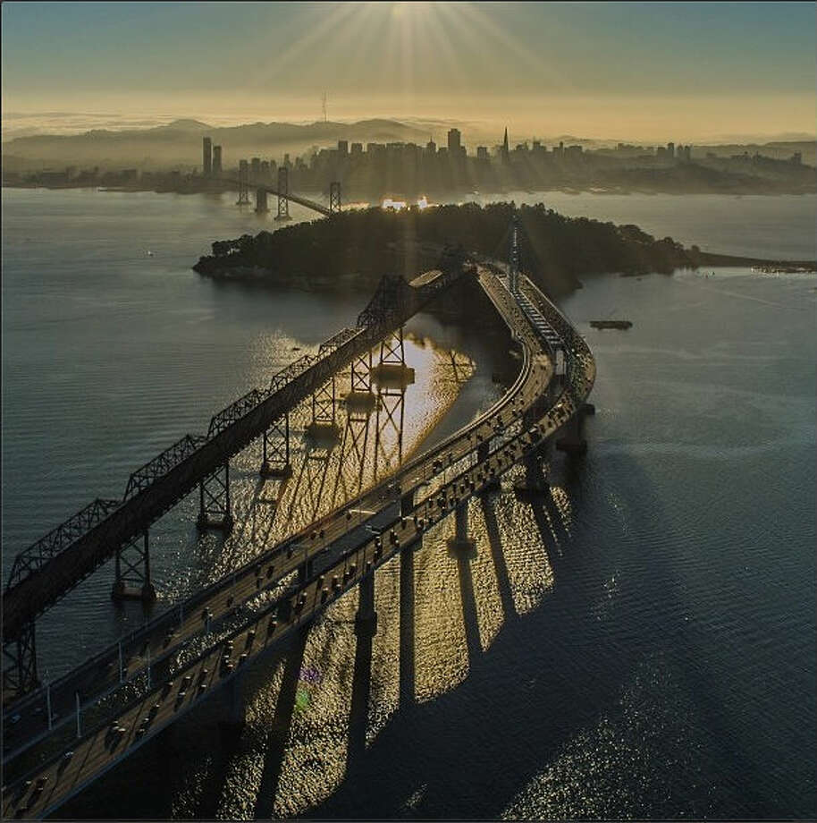 "Chris H. continued his aerial endeavors to snap this photo of the Bay Bridge with Treasure Island and the San Francisco skyline in the background. He writes: ""I took a helicopter flight over San Francisco on my last birthday, this was by far the best flight ever over the city I live in and love."""