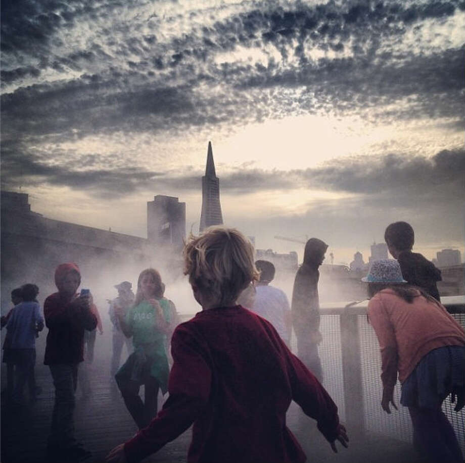 "Pauly H., who goes by @bigpaulyfilms, took this surreal-looking photo at the Fog Bridge in the Exploratorium. As Pauly says, the photo exudes an ""end of the world"" feel in front of the San Francisco skyline."