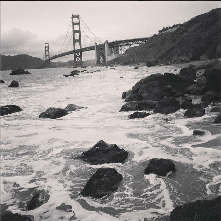 "Garrett Y.W., or @thewoodlands on Instagram, took this black and white photo of the Golden Gate Bridge from Marshall's Beach. Garrett writes, ""This photo shows a bit of the depth and character the fog gives to the city."""