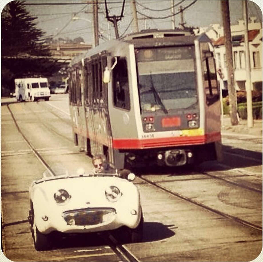 "San Francisco can be a city of many contrasts. Bill D., who goes by @honeybilld, snapped this photo right outside his home at San Jose Ave. at Santa Rosa in the Mission Terrace neighborhood. He says, ""I loved the contrast of the huge train behind the tiny sports car."""