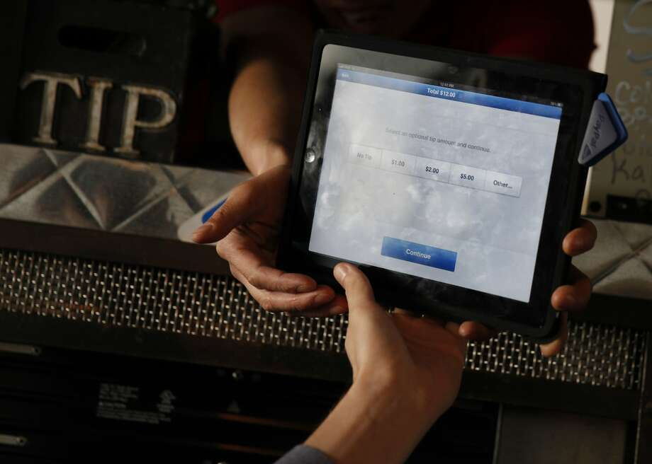 Above: A server hands a customer a tablet to make a mobile payment at the Boneyard barbecue truck in San Francisco on Feb. 19. Photo: Lea Suzuki, The Chronicle
