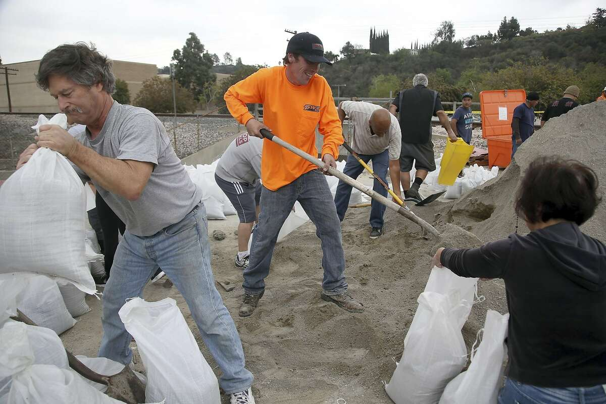 Volunteers, from left, Steve Hamilton, Thomas Lubboch and Becky Chen help fill sandbags before an expected storm Wednesday Feb. 26, 2014 in Glendora, Calif. Much-needed rain fell in Northern California on Wednesday at the outset of what the parched state hopes is the start to a one-two punch of stormy weather with a half inch of rain predicted. (AP Photo/Nick Ut )