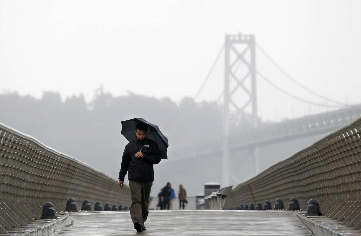 A man walks down Pier 14 during a rain storm in San Francisco, California, February 26, 2014. REUTERS/Beck Diefenbach (UNITED STATES - Tags: ENVIRONMENT SOCIETY)
