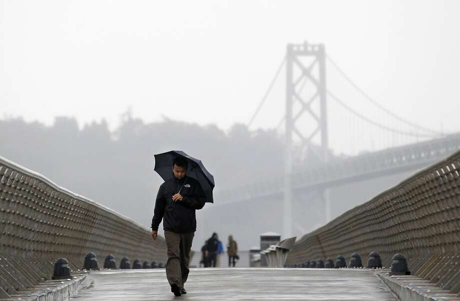 A man walks down Pier 14 during a rain storm in San Francisco, California, February 26, 2014. Photo: Beck Diefenbach, Reuters
