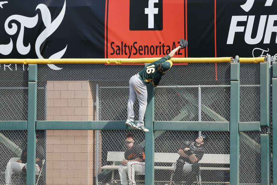 The A's Josh Reddick went high off the ground to rob the Giants' Michael Morse in the second inning in their spring opener. Photo: Michael Macor, The Chronicle